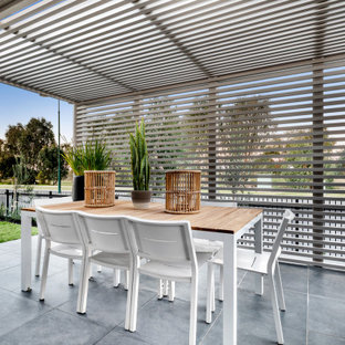 Design ideas for a beach style patio in Other with tile and a pergola.