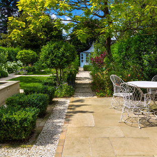 This is an example of a medium sized traditional back patio in London with natural stone paving.