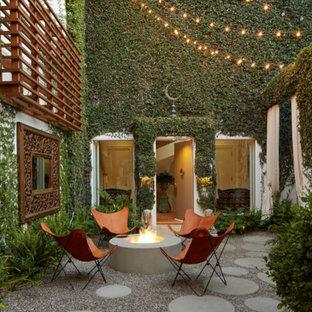 Ispirazione per un patio o portico eclettico di medie dimensioni e in cortile con un focolare, ghiaia e nessuna copertura