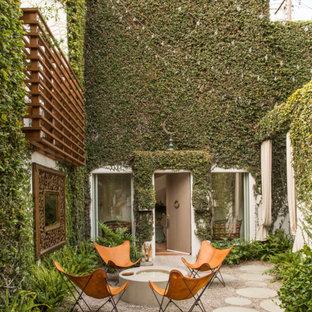 Esempio di un patio o portico eclettico con un focolare e nessuna copertura