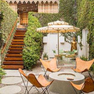 Idee per un patio o portico bohémian di medie dimensioni e in cortile con un focolare, ghiaia e nessuna copertura
