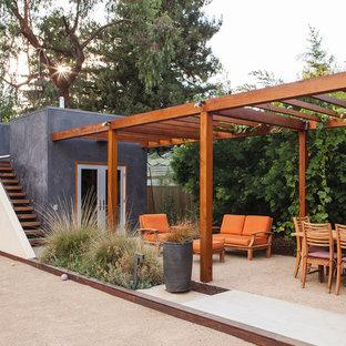Immagine di un patio o portico minimal con graniglia di granito e una pergola