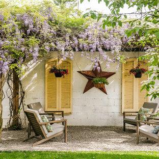 Modelo de patio romántico con gravilla y pérgola