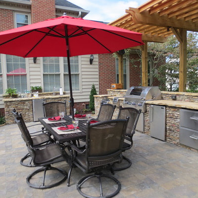 Example of a mid-sized classic backyard stone patio kitchen design in Charlotte with a pergola