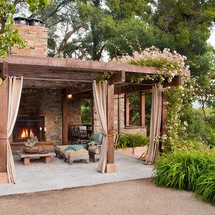 Cette image montre une terrasse arrière méditerranéenne de taille moyenne avec une pergola, des pavés en pierre naturelle et une cheminée.