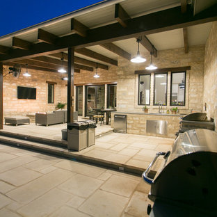 Photo of a farmhouse patio in Austin with a fire feature, natural stone paving and an awning.