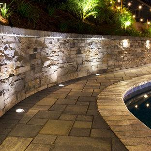 Foto di un grande patio o portico moderno dietro casa con pavimentazioni in pietra naturale e una pergola
