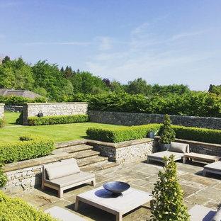 Ispirazione per un ampio patio o portico chic dietro casa con pavimentazioni in pietra naturale e nessuna copertura