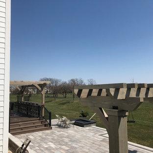 Idee per un ampio patio o portico bohémian dietro casa con un focolare, pavimentazioni in mattoni e una pergola