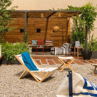 Ejemplo de patio contemporáneo, grande, en patio trasero, con jardín de macetas, gravilla y pérgola