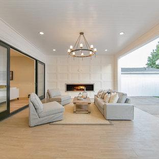 Inspiration pour une grande terrasse arrière craftsman avec un foyer extérieur, du carrelage et une extension de toiture.