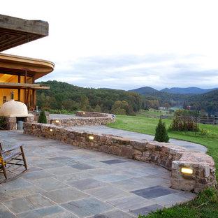 Esempio di un patio o portico stile rurale dietro casa con nessuna copertura, un focolare e pavimentazioni in pietra naturale