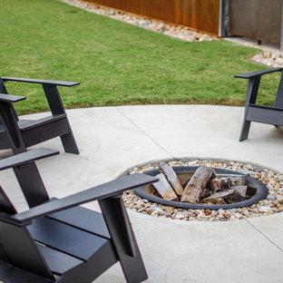 Ispirazione per un piccolo patio o portico contemporaneo dietro casa con un focolare, lastre di cemento e nessuna copertura