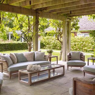 Ispirazione per un grande patio o portico chic dietro casa con pavimentazioni in pietra naturale e una pergola