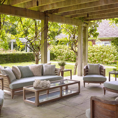 Patio - large traditional backyard stone patio idea in New York with a pergola