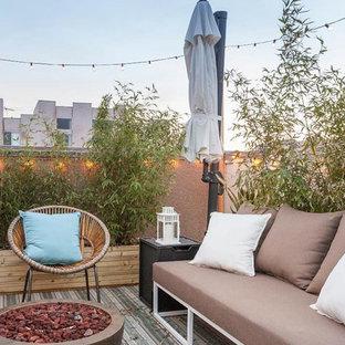 Ispirazione per un piccolo patio o portico eclettico con un focolare, lastre di cemento e nessuna copertura