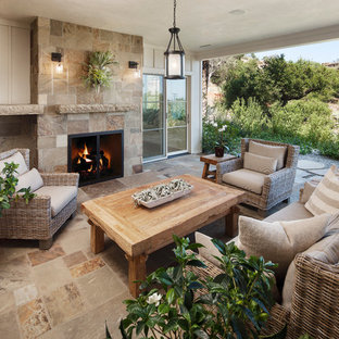 Mid-sized elegant backyard stone patio photo in Santa Barbara with a fire pit and a roof extension