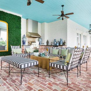 Idee per un grande patio o portico classico dietro casa con pavimentazioni in mattoni e un tetto a sbalzo