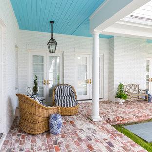 Esempio di un grande patio o portico tradizionale dietro casa con pavimentazioni in mattoni e un tetto a sbalzo