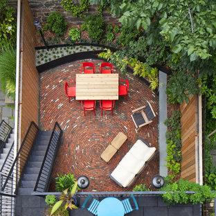Immagine di un piccolo patio o portico eclettico dietro casa con pavimentazioni in mattoni
