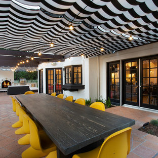 This is an example of a medium sized bohemian side patio in Los Angeles with an outdoor kitchen, an awning and tiled flooring.