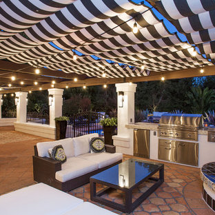 Large mediterranean back patio in Los Angeles with an outdoor kitchen, an awning and tiled flooring.