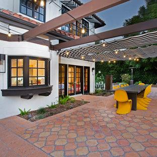 Immagine di un patio o portico boho chic di medie dimensioni e nel cortile laterale con piastrelle e un parasole