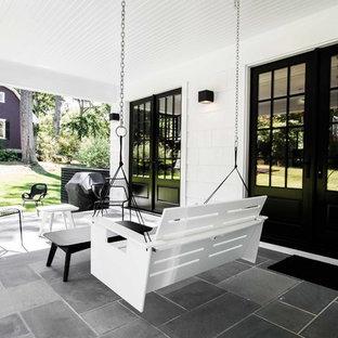 Idee per un patio o portico eclettico di medie dimensioni e dietro casa con cemento stampato e un tetto a sbalzo