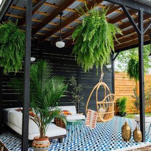 Foto de patio bohemio con suelo de baldosas y cenador