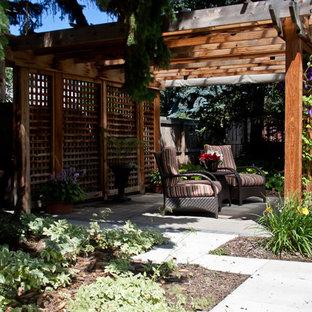 Ispirazione per un grande patio o portico eclettico dietro casa con pavimentazioni in mattoni e una pergola