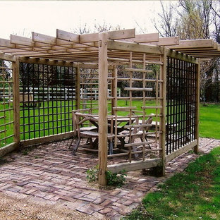 Example of a small eclectic backyard brick patio design in Minneapolis with a pergola