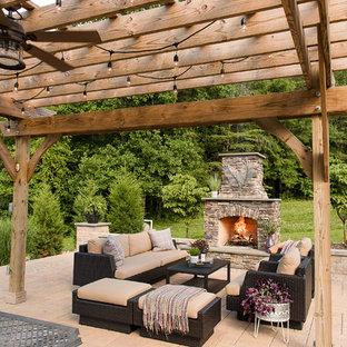 Idée de décoration pour une grande terrasse arrière chalet avec une cheminée, des pavés en béton et une pergola.