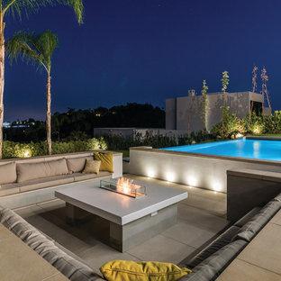 Modelo de patio moderno, grande, sin cubierta, en patio trasero, con brasero