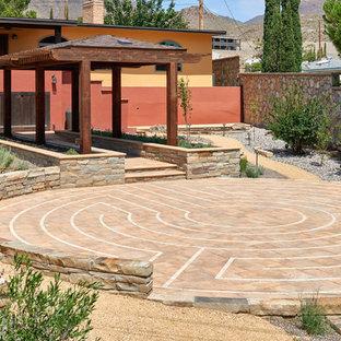 Immagine di un patio o portico tradizionale dietro casa con pavimentazioni in cemento e un gazebo o capanno
