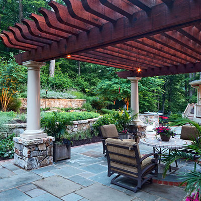 Example of a mid-sized classic backyard concrete paver patio design in DC Metro with a pergola