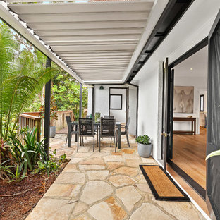 Inspiration for a mid-sized transitional backyard patio in Sydney with natural stone pavers and an awning.