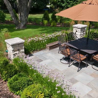 Patio - mid-sized traditional backyard stone patio idea in Milwaukee