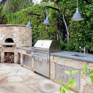 Ispirazione per un patio o portico minimal di medie dimensioni e dietro casa con pavimentazioni in pietra naturale e una pergola