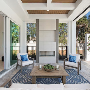 Réalisation d'une terrasse arrière marine avec un foyer extérieur, du carrelage et une extension de toiture.