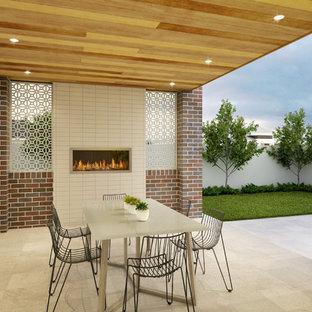 Foto di un patio o portico minimalista di medie dimensioni e dietro casa con un caminetto, pavimentazioni in pietra naturale e un tetto a sbalzo