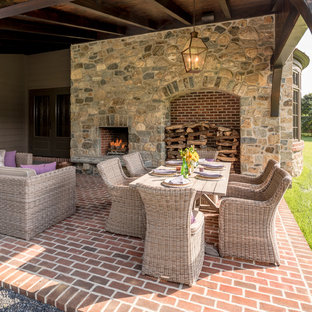 Patio - small traditional side yard brick patio idea in Wilmington with a roof extension and a fireplace
