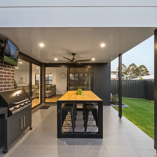 Inspiration for a contemporary backyard patio in Other with tile and a roof extension.