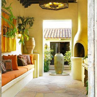Esempio di un patio o portico mediterraneo in cortile con un tetto a sbalzo, un focolare e pavimentazioni in pietra naturale