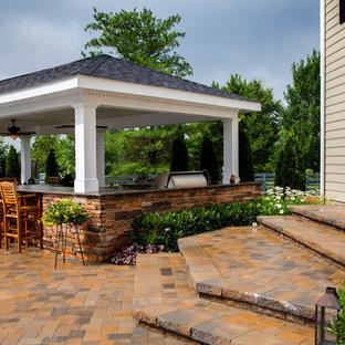 Large elegant backyard stone patio kitchen photo in Orange County with a gazebo