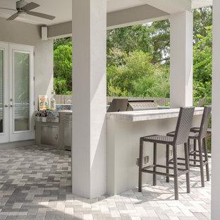 Idee per un patio o portico tradizionale di medie dimensioni e dietro casa con pavimentazioni in mattoni e un tetto a sbalzo