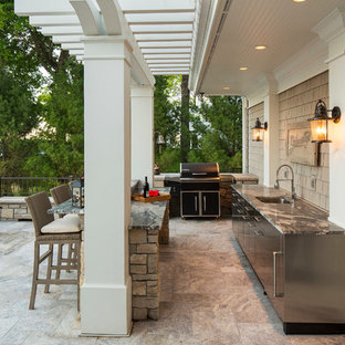 Patio kitchen - large craftsman backyard concrete paver patio kitchen idea in Minneapolis with a pergola