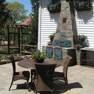 Patio kitchen - small traditional backyard stone patio kitchen idea in Newark