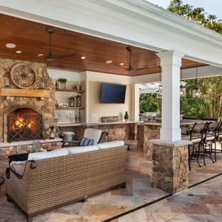 Photo of a large traditional backyard patio in DC Metro with with fireplace and a roof extension.