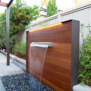 Immagine di un piccolo patio o portico design in cortile con fontane, pavimentazioni in cemento e una pergola