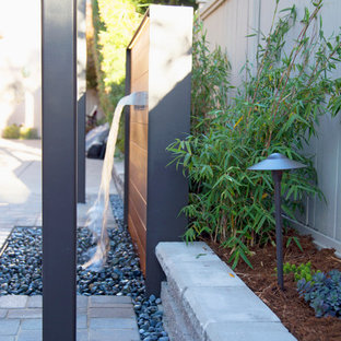 Small contemporary courtyard patio in San Luis Obispo with a water feature, concrete pavers and a pergola.